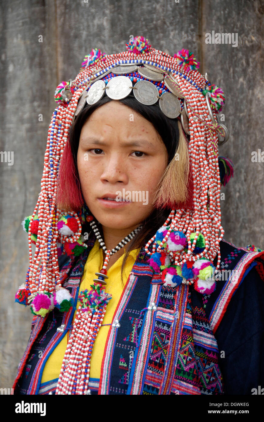 Portrait, woman of the Ya-Er Akha ethnic group, traditional clothing, colorful headdress with silver coins - Stock Image