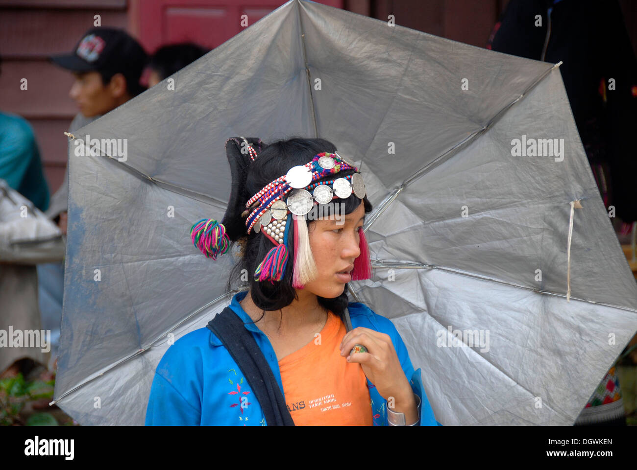 Young Woman of the Ya-Er Akha ethnic group with an umbrella, traditional clothing, headdress with silver coins, Pak Nam Noi - Stock Image