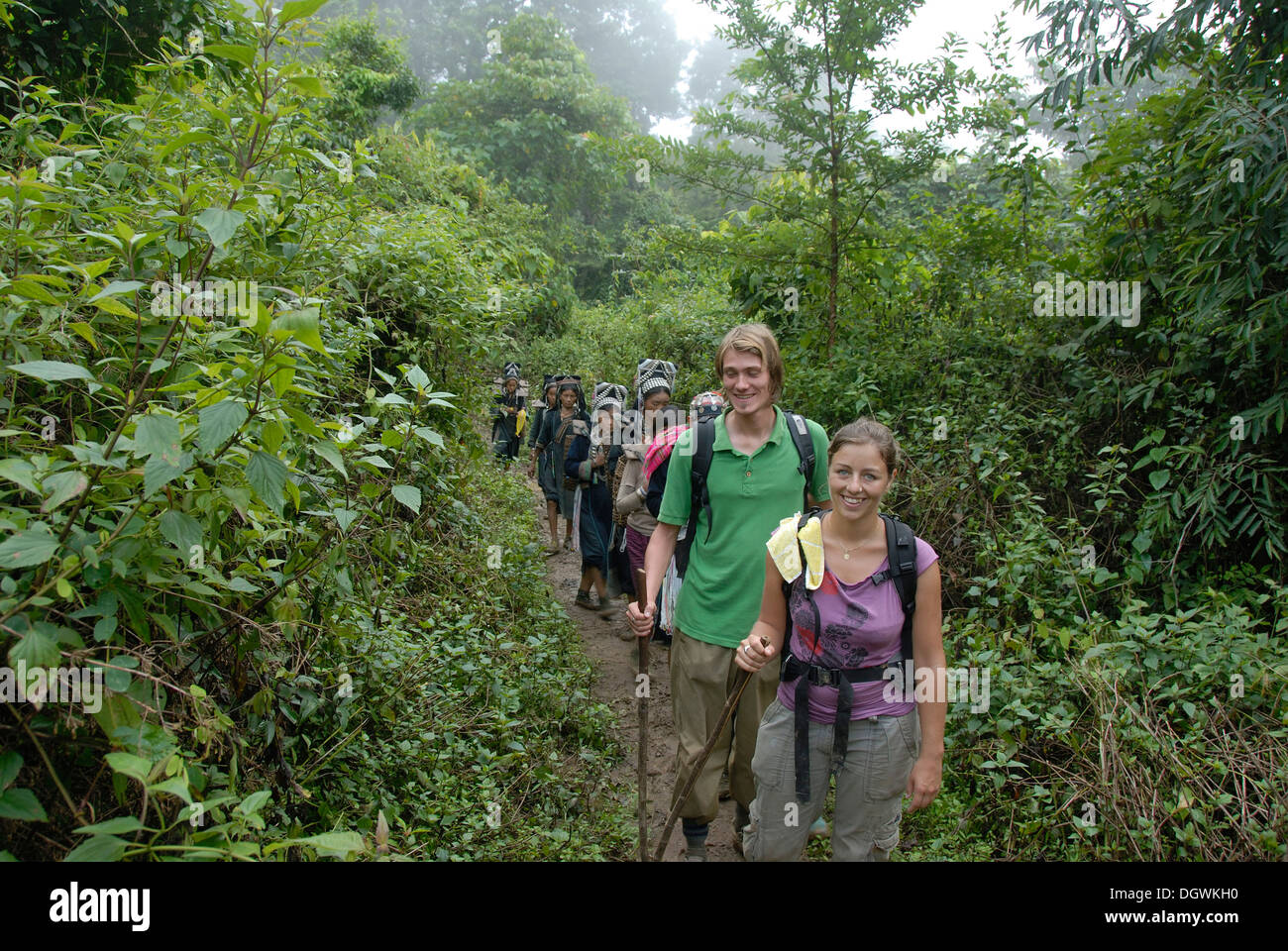 Trekking, smiling Western tourists with women of the Akha Nuqui ethnic group, jungle track at Ban Phou Yot - Stock Image