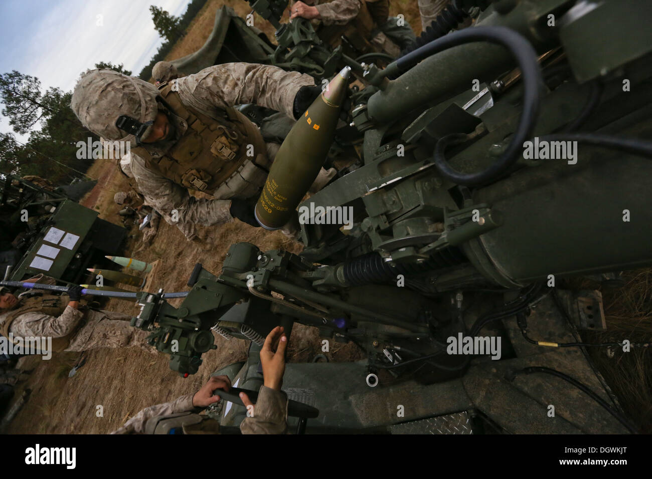 U.S. Marine Corps Lance Cpl. Jacob Carmona, a rammer with India Battery, 3rd Battalion, 10th Marines, loads a high explosive round into the loading tray of an M777 Howitzer during Operation Rolling Thunder aboard Ft. Bragg, N.C., Oct 18, 2013. 10th Marine - Stock Image