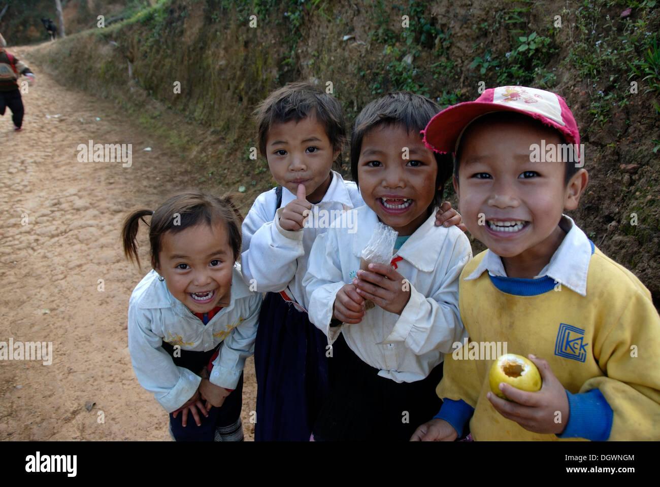 Children, poverty, gang of grinning children having fun, village of Ban Komaen, Phongsali district and province, Laos - Stock Image