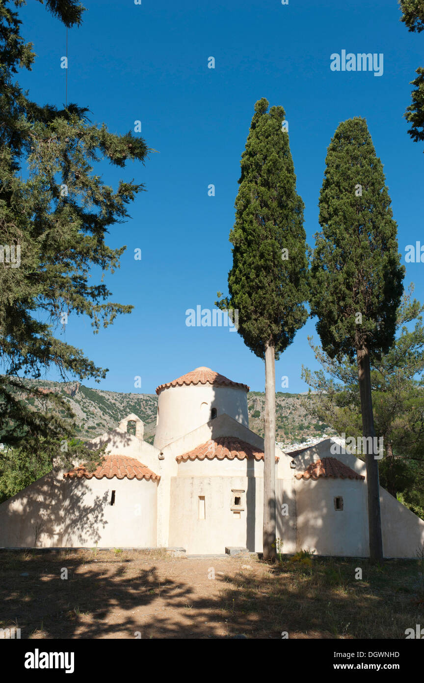 A three-aisled Greek Orthodox domed church, rear side, Monastery of Panagia i Kera, two tall Cypress trees (Cupressus) in the - Stock Image