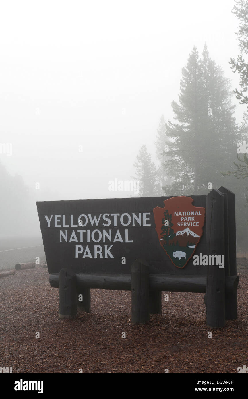 Entrance, wooden sign in the fog, National Park Service, west entrance, Yellowstone National Park, West Yellowstone, Montana - Stock Image