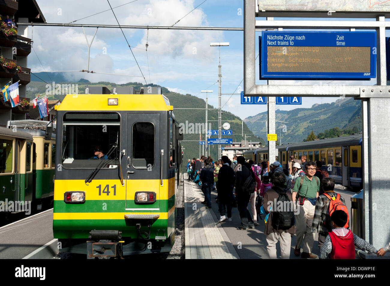 Train and travellers on the platform of the railway station of Grindelwald, Bernese Oberland, Canton of Bern, Alps, Switzerland - Stock Image
