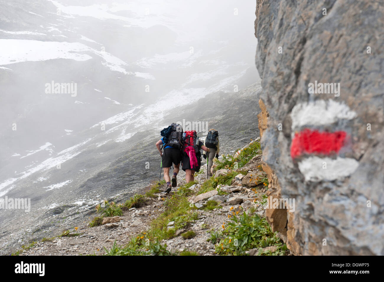 Red and white markings on rocks, Bear Trek hiking trail, hikers on the way up to the pass in the fog, Pass Hohtürli, Kandersteg - Stock Image