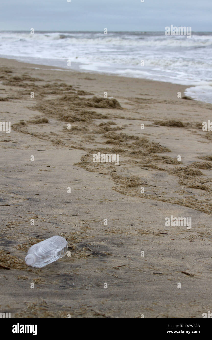 A plastic water bottle washed up onto a beach in Nags Head in the Outer Banks of North Carolina, USA - Stock Image