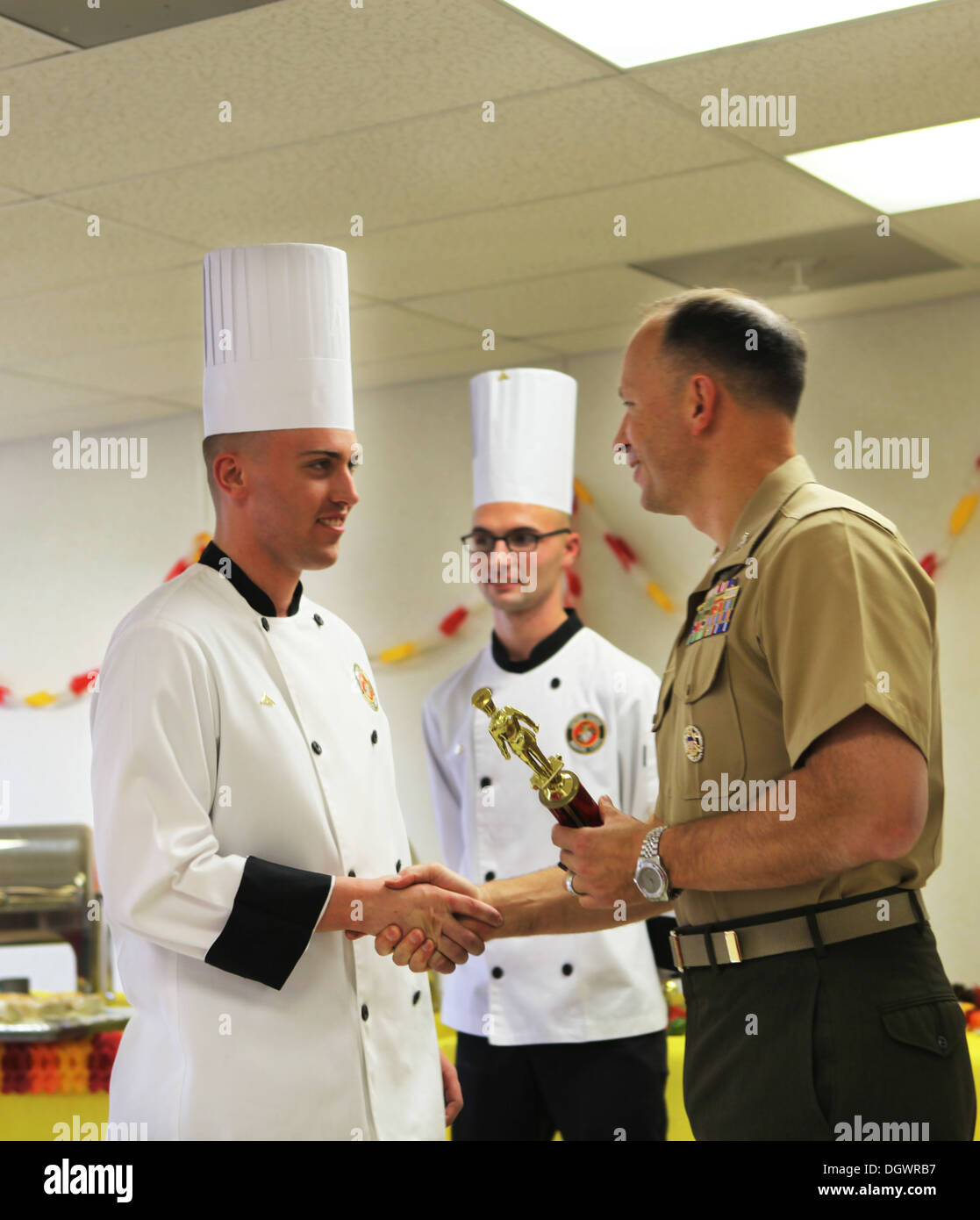 Lance Cpl. Zachery C. Schram receives the 1st place award from Col. Chris Pappas III, the commanding officer of Marine Corps Air Station Cherry Point during the Chef of the Year competition Oct. 18. - Stock Image
