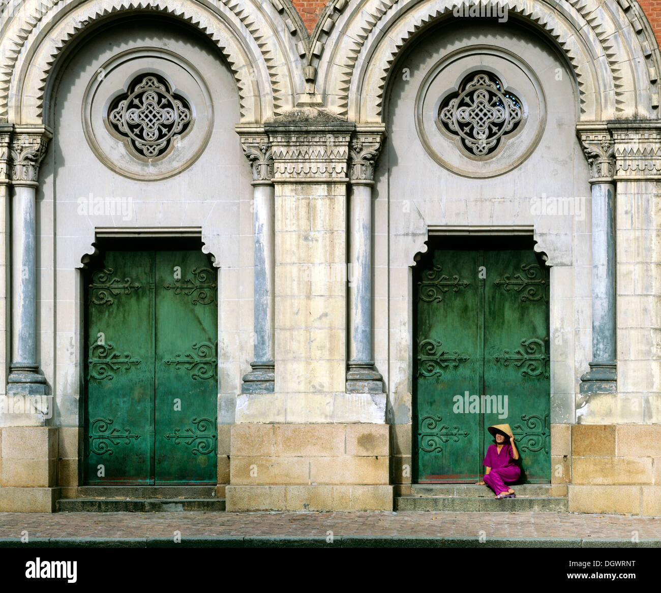 Notre Dame, neo-Romanesque cathedral, woman with cone hat sitting at the side entrance portal, Saigon, Ho-Chi-Minh-Stadt - Stock Image