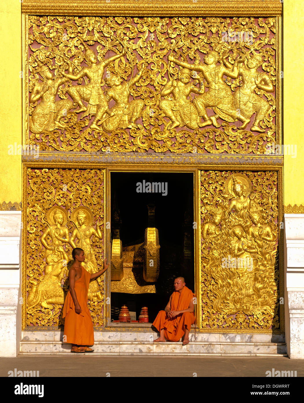 Golden reliefs, monks at the entrance to the Carriage House, Wat Xieng Tong or Vat Xienthong, Luang Prabang - Stock Image