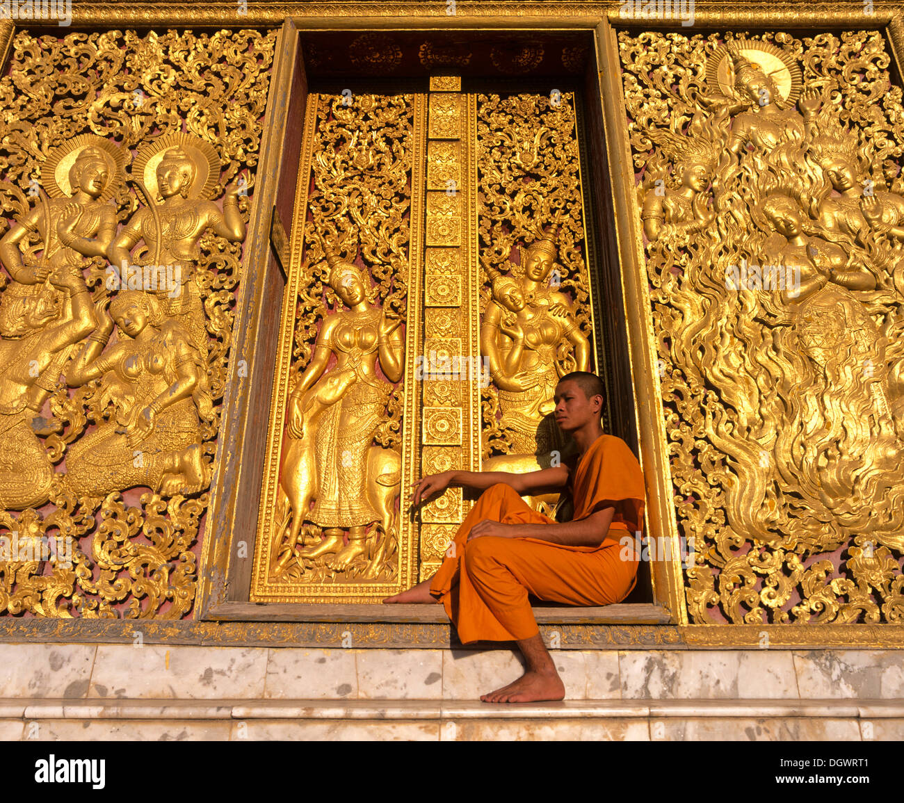 Golden reliefs, monk at the entrance to the Carriage House, Wat Xieng Tong or Vat Xienthong, Luang Prabang - Stock Image