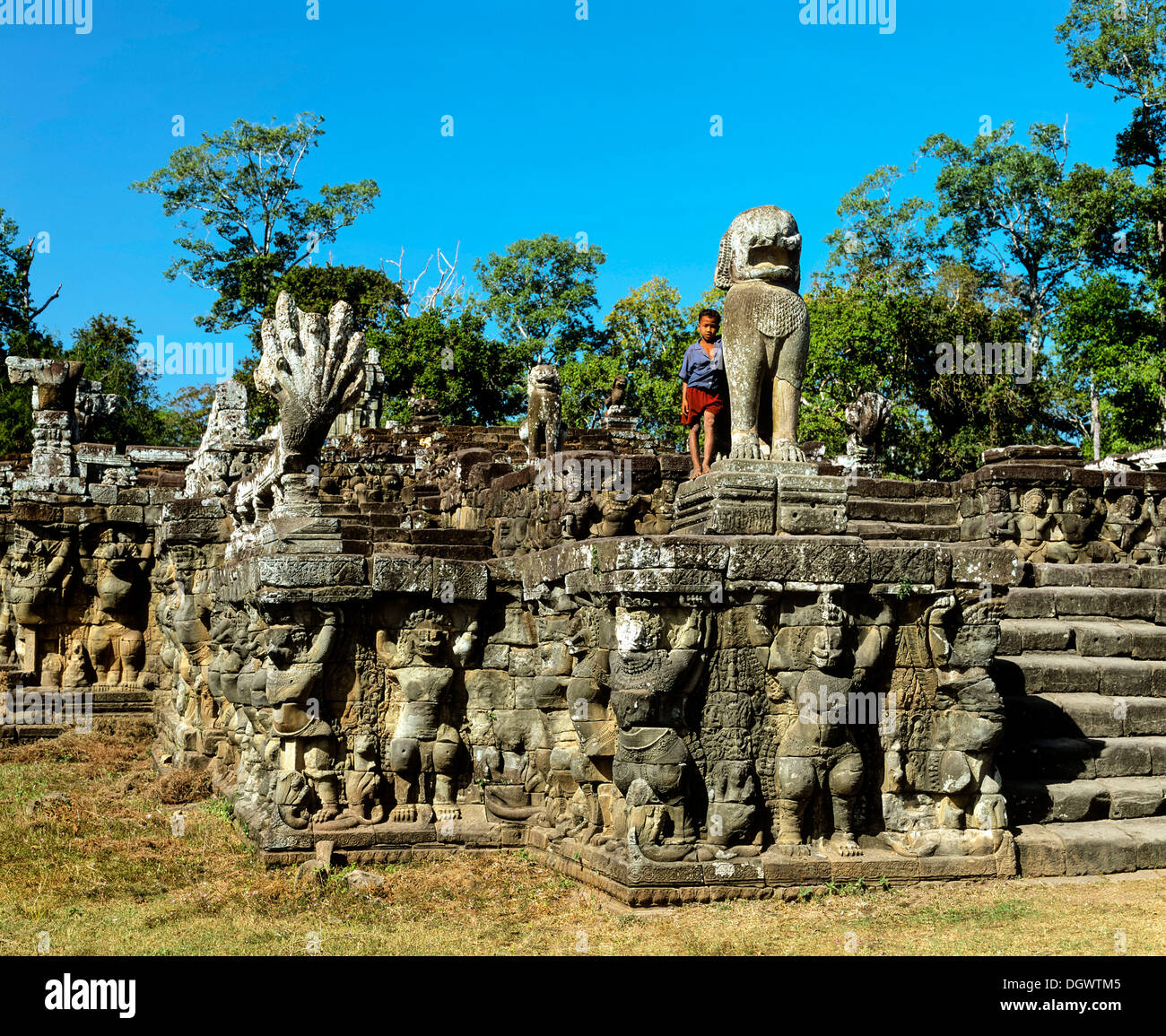 Boy on the Terrace of the Elephants, wall-reliefs with garudas and lions at the Royal Palace, Angkor Thom, Siem Reap Province - Stock Image