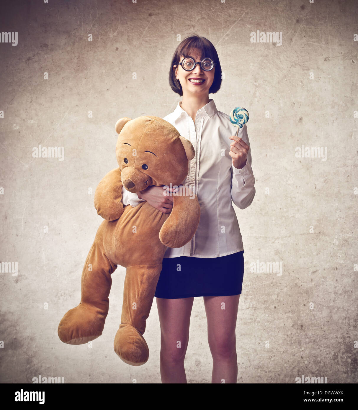 Nerd girl holding a teddy and a lollipop - Stock Image