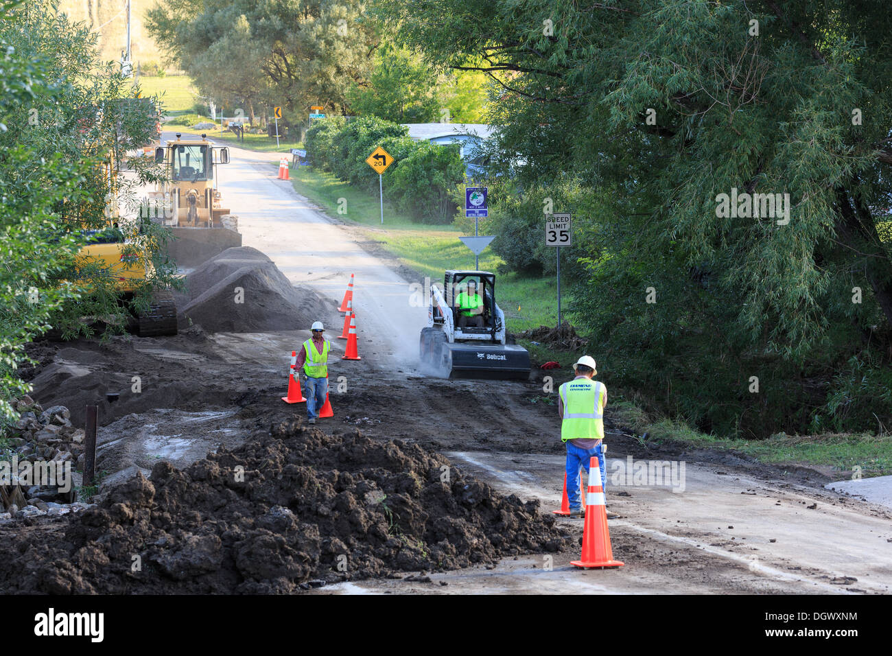 A work crew repairs a road damaged by flood water in Arvada, Colorado - Stock Image