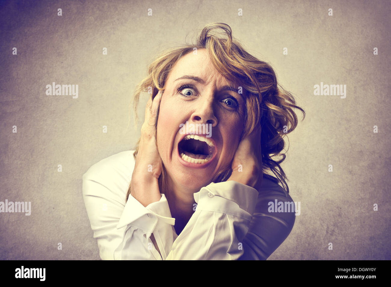 Portrait of a desperate blonde woman screaming - Stock Image