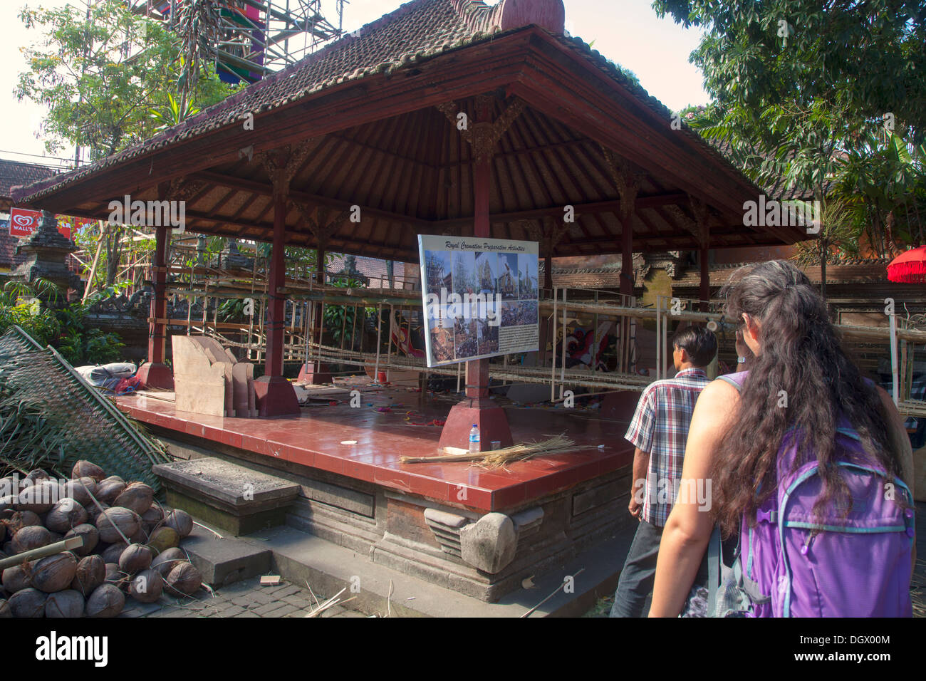 Tourist observe pavilion religious sign Ubud Bali Indonesia Asia construction site wooden make create unfinished works look read - Stock Image