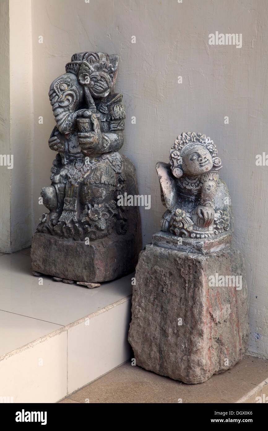 Two statues display outside giftshop Ubud Bali Indonesia Asia gifts sculptures stone curved curving art artist tourist items art - Stock Image