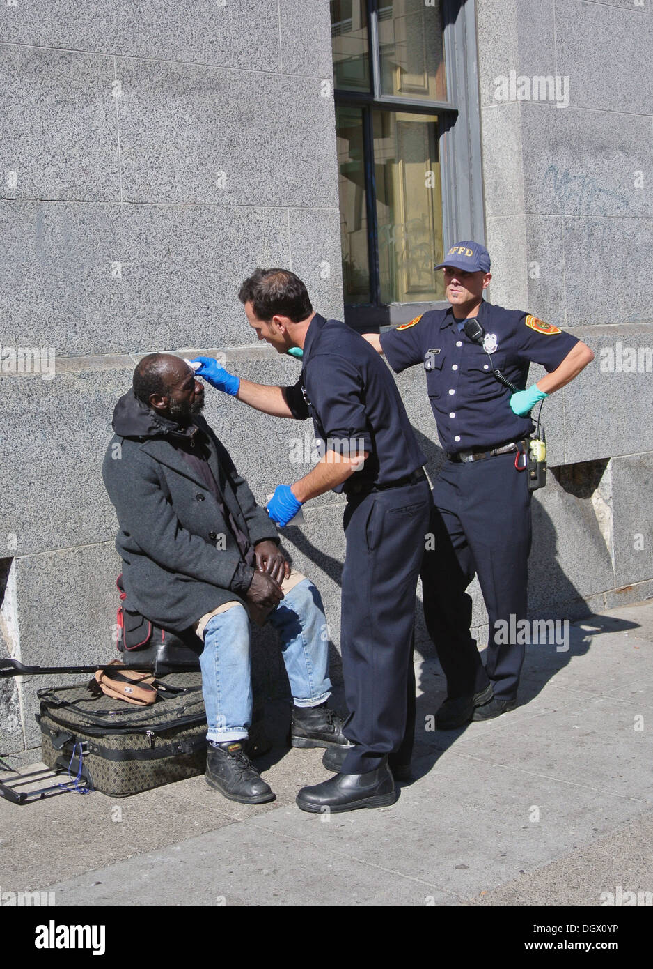 San Francisco policemen provide first aid to homeless man in the Tenderloin - Stock Image