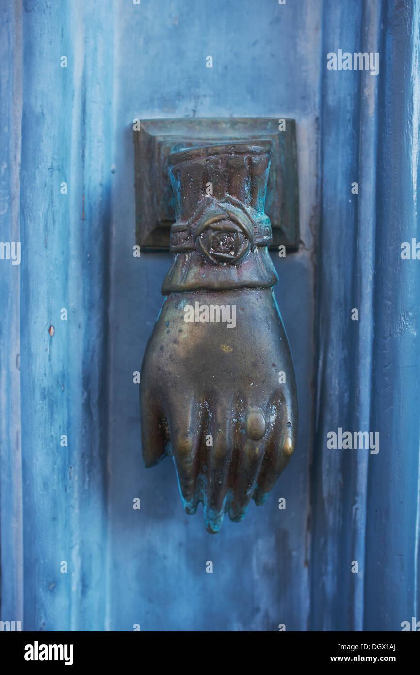 Ornate Brass Hand Door Knocker On A Blue Painted Door In Europe   Stock  Image