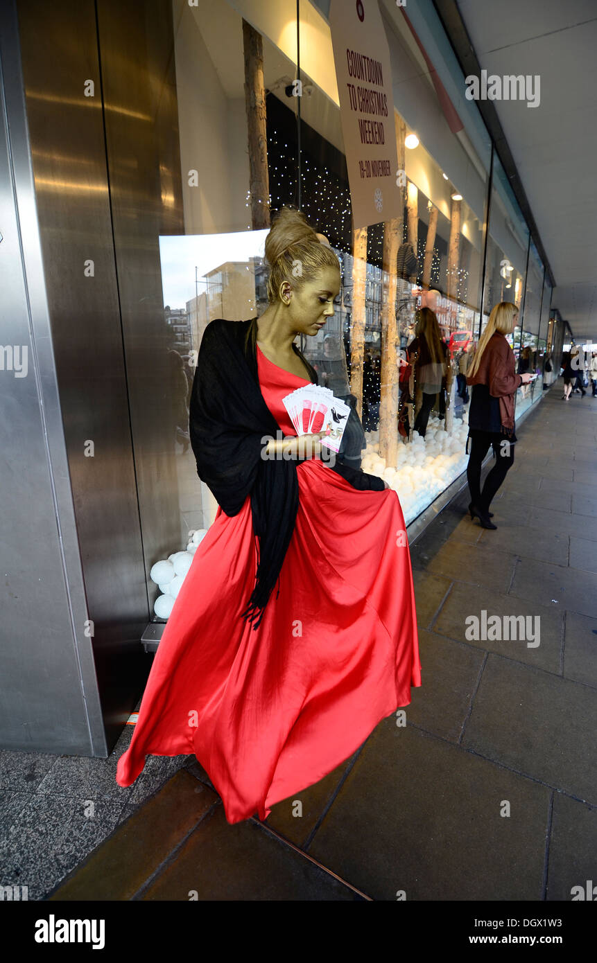Attractive girl in red dress and gold body paint with leaflets on Oxford street, London - Stock Image