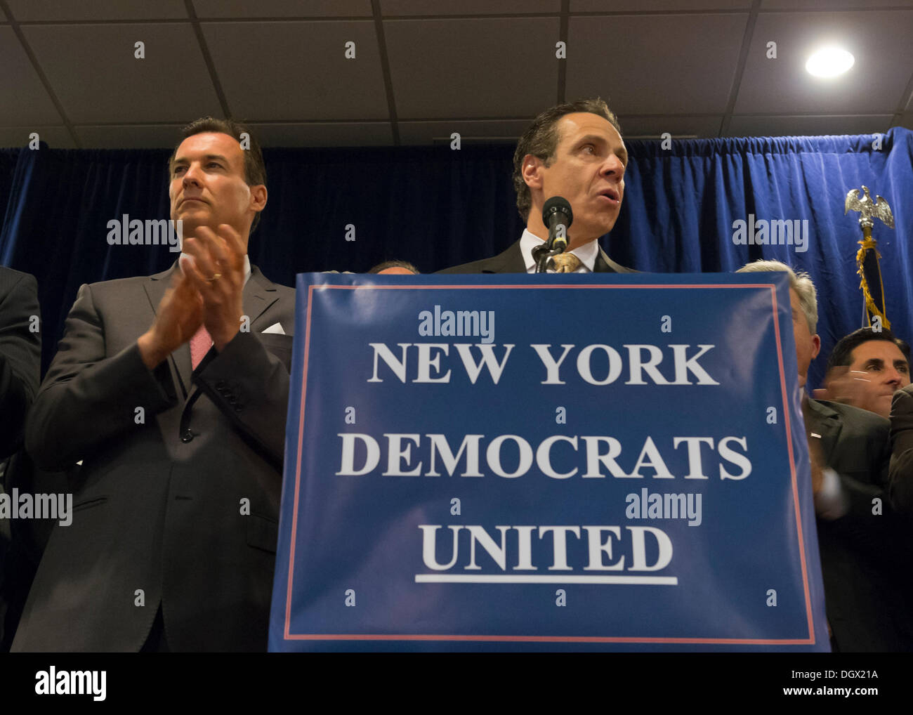 Albertson, New York, U.S. 26th October 2013. New York Governor ANDREW CUOMO, at podium, endorses TOM SUOZZI, left of him, for Nassau County Executive, with supporters, including veterans, union members, and Democratic candidates for office in Nassau and Suffoilk Counties in Long Island, filling the announcement room at the Albertson Veterans of Foreign Wars VFW Post. Democrat Suozzi, the former Nassau County Executive, and Republican encumbant Mangano face each other in a rematch in the upcoming November 5th election. © Ann E Parry/Alamy Live News - Stock Image