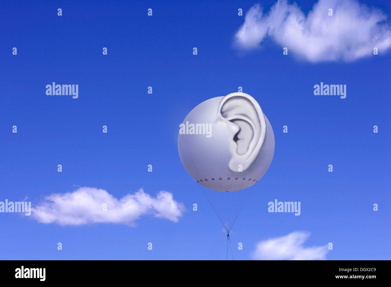 Tethered balloon with a three-dimensional human ear against a blue sky with white clouds, symbolic image for bugging or spying - Stock Image