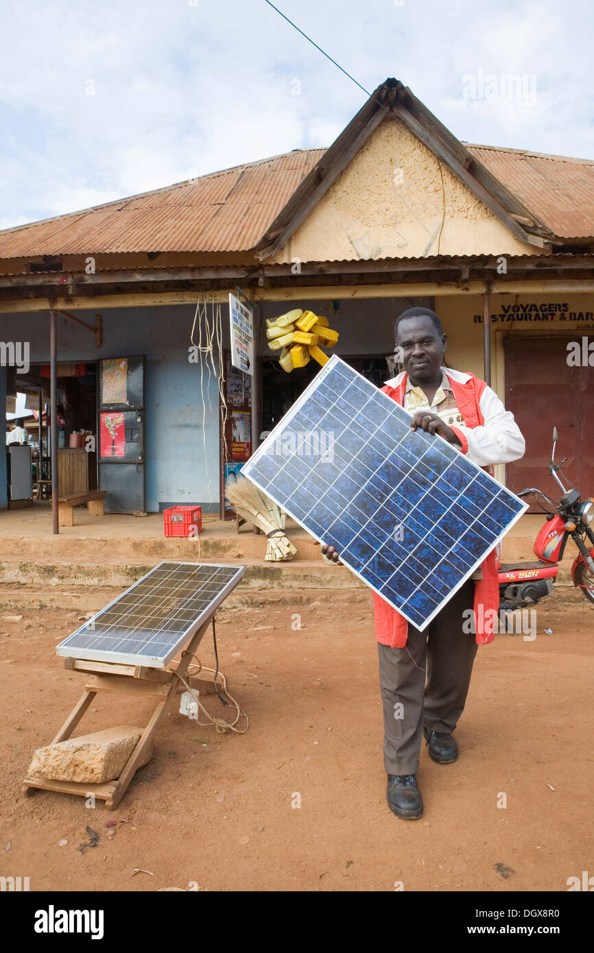 Mr. Tinkasimire, owner of an electrical shop, offering products like Premier Modul solar panels, Masindi, Uganda, Africa - Stock Image