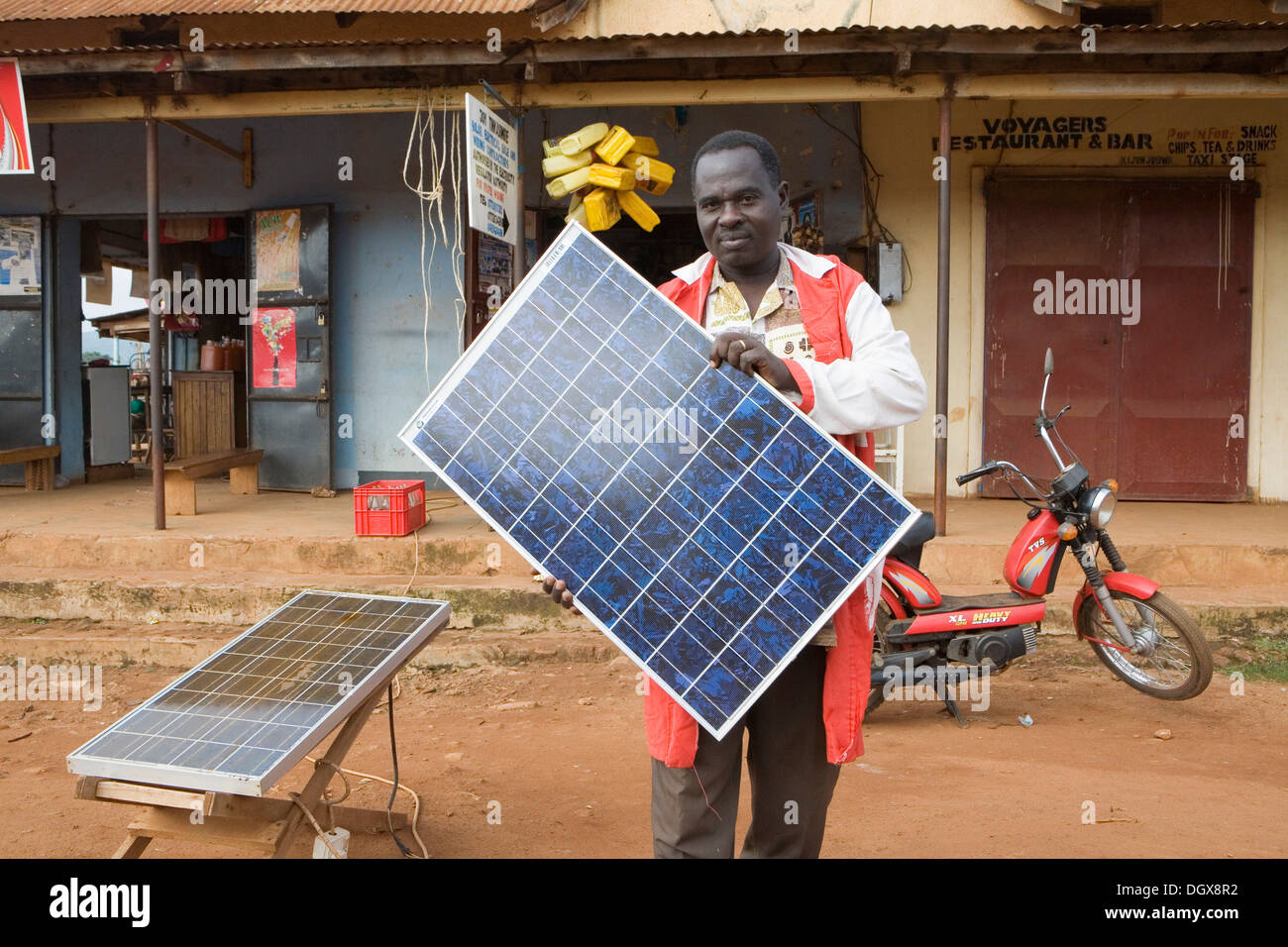 Mr. Tinkasimire, owner of an electrical shop, offering products like Premier Modul solar panels, Masindi, Uganda, Stock Photo