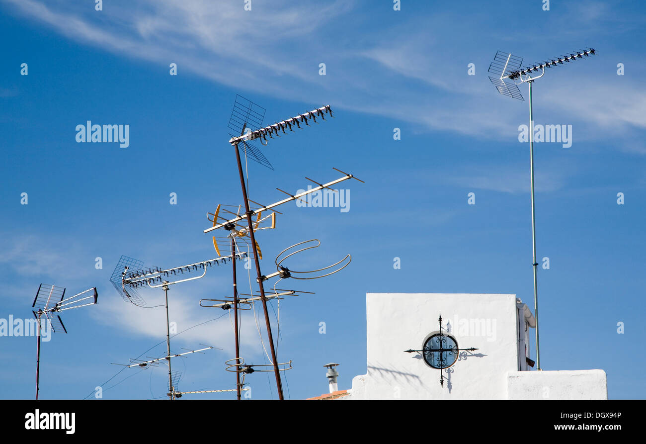 Variety of television aerials on rooftops against blue sky Spain - Stock Image