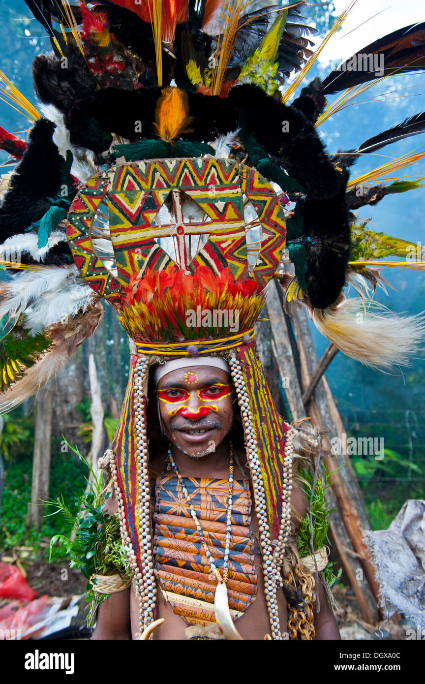 Man with a huge headdress, colourful decorations and face paint is celebrating at the traditional Sing Sing gathering in the - Stock Image