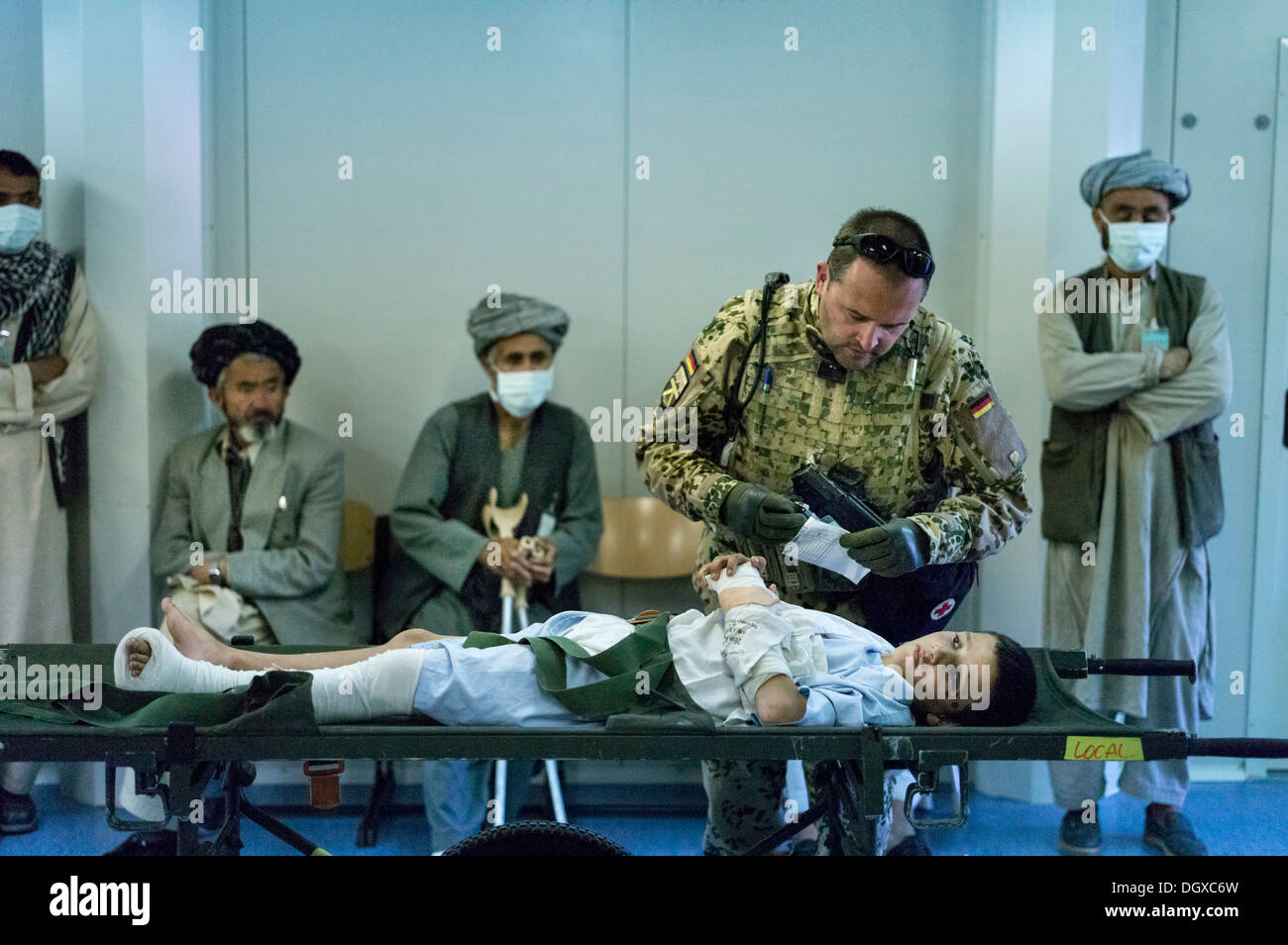 Bundeswehr doctor treating an Afghan boy in PRT Feyzabad, a field hospital of the Federal Defence Forces of Germany, Feyzabad - Stock Image