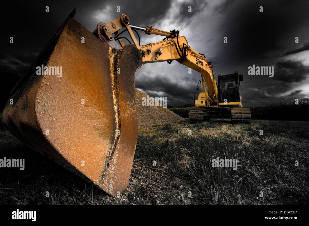 Backhoe bucket excavators with a dramatic sky Stock Photo