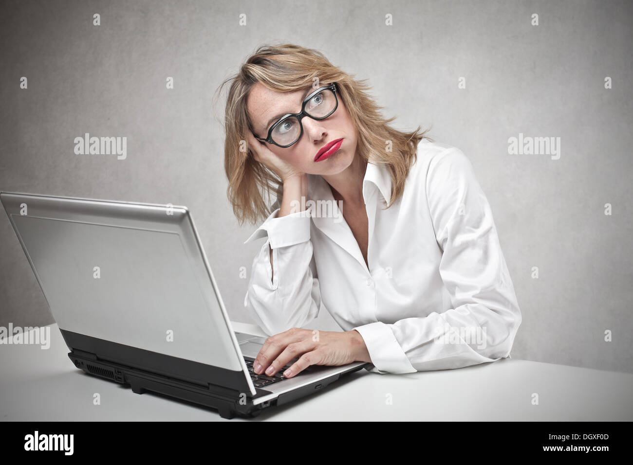Bored blonde woman with glasses using a laptop Stock Photo