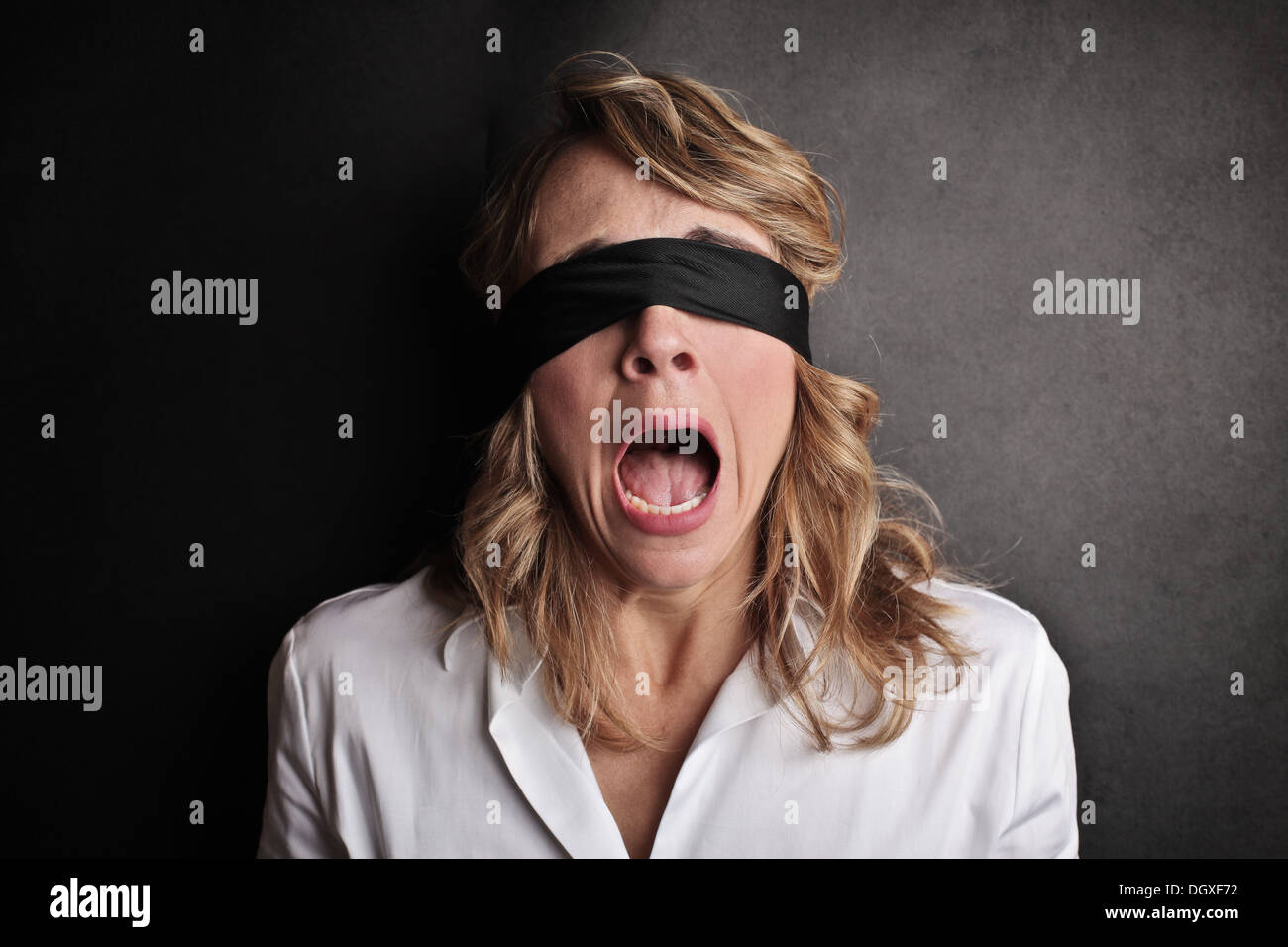 Scared woman blindfolded screaming - Stock Image