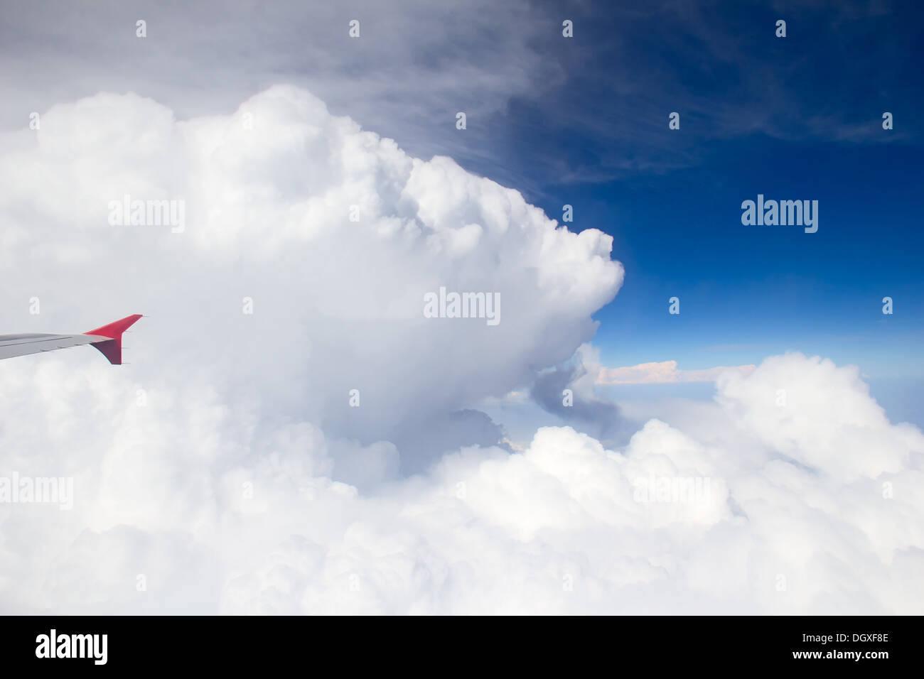 Wing of airplane flying above the clouds in the sky - Stock Image