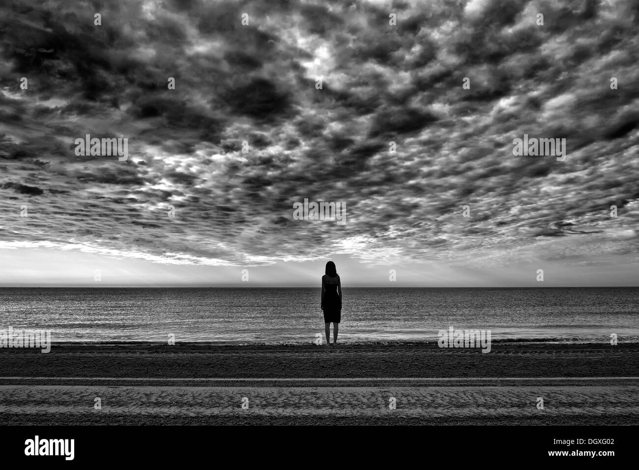Woman wearing a black dress standing by the sea, moody clouds, Cavallino, Jesolo, Venedig, Italy - Stock Image