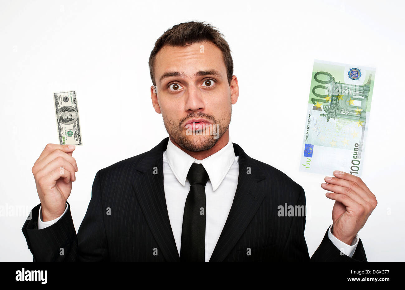 Frustrated young man wearing a suit holding a small 100 dollar bill ...