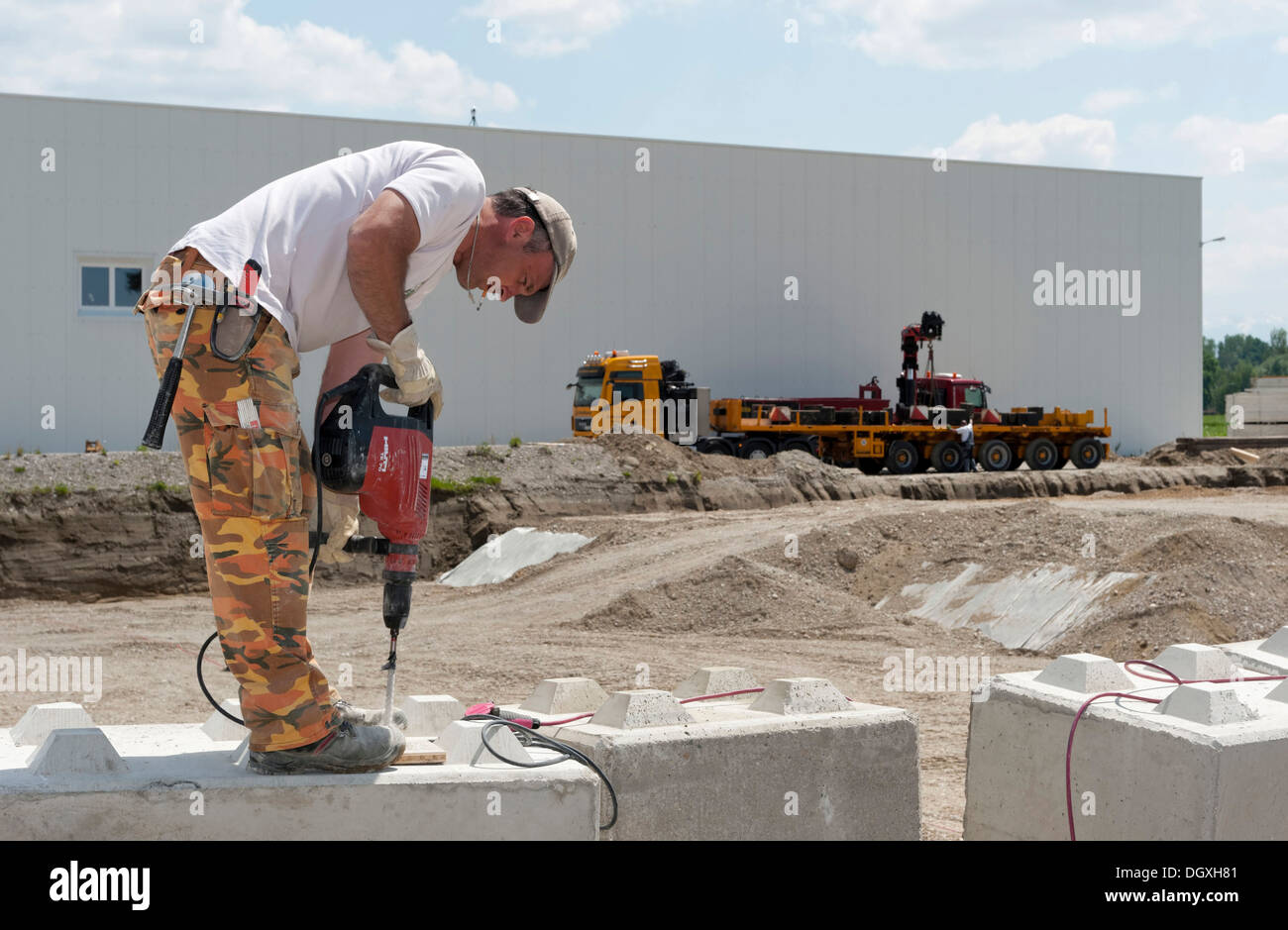 Construction worker drilling holes into stone blocks that ...  Construction wo...