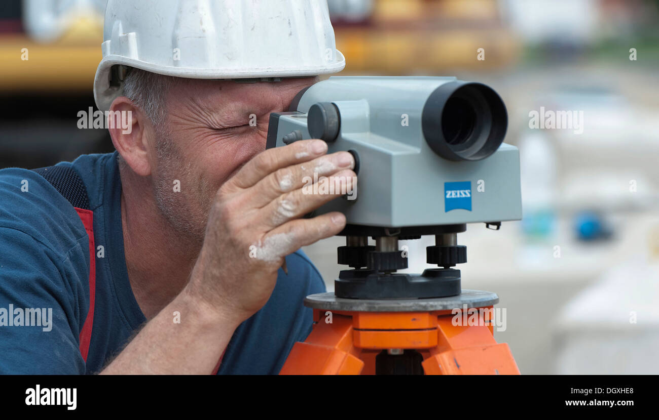 A structural engineer is taking measurements of a possible soil dropping during a building site load test, at a construction - Stock Image
