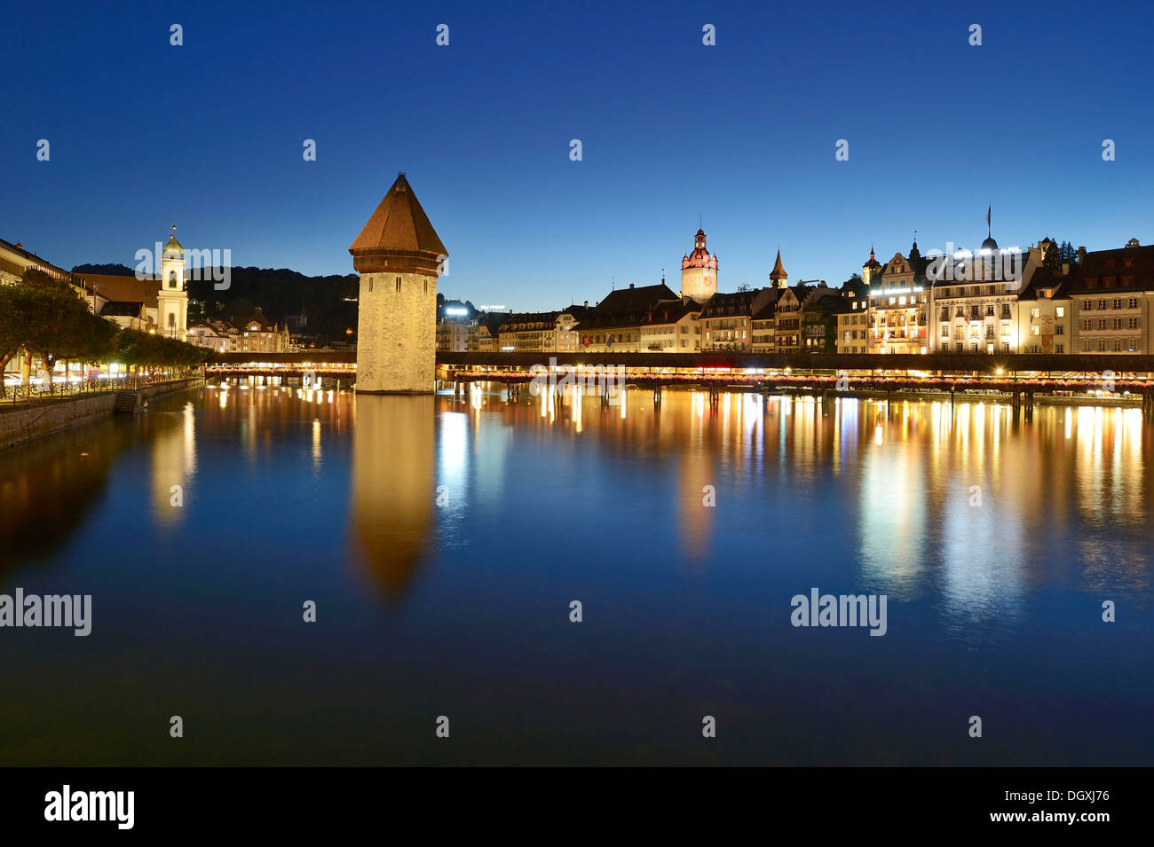 The lights of Chapel Bridge and the water tower are reflected in the water of the Reuss river, Lucerne, Switzerland, Europe - Stock Image