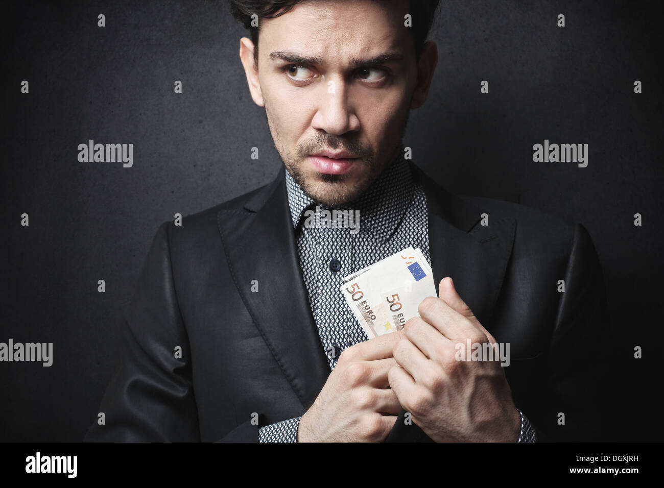 Elegant man hiding fifty euro banknotes in his suit jacket - Stock Image