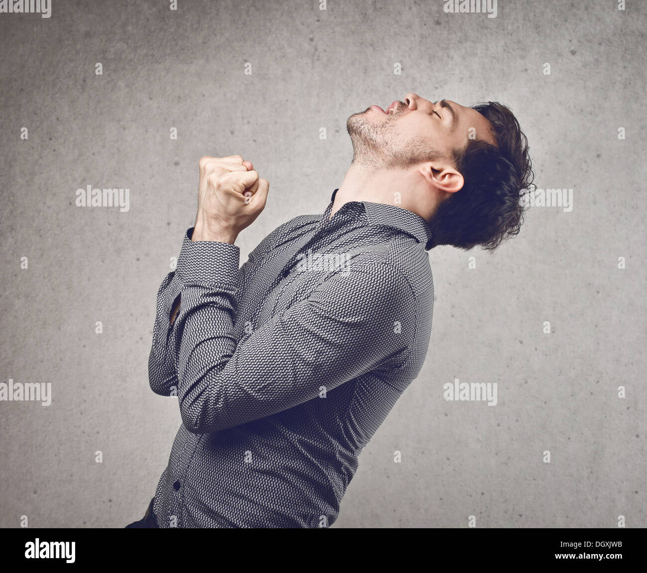 Young man in grey shirt rejoicing for his success - Stock Image