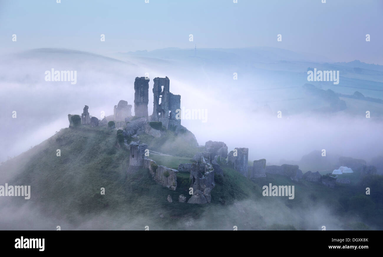 Corfe Castle rising through early morning mists - Stock Image