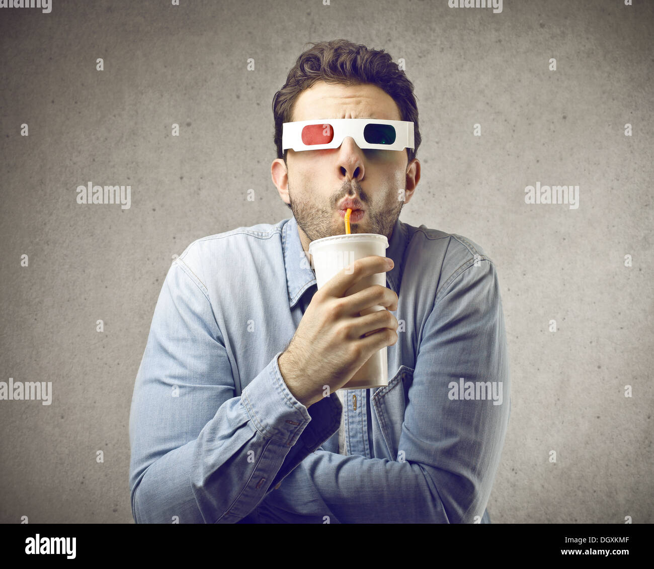 Man with tridimensional glasses drinking a soda with a straw - Stock Image