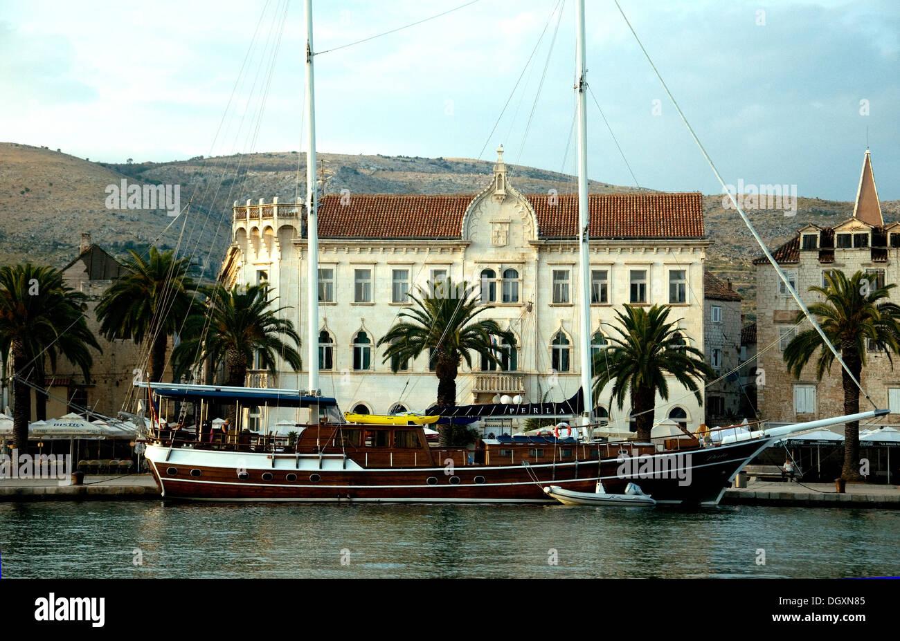 Venetian elegance dominates historic Trogir in Croatia's Dalmatian coast where a stylish gulet, sailing boat, adorns the quay - Stock Image