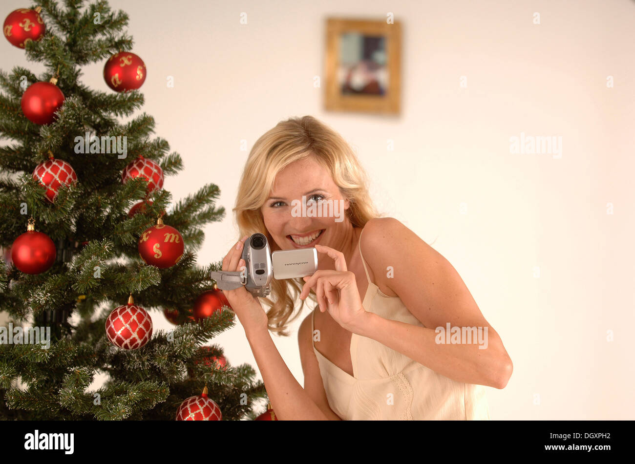 Blonde woman, 20-30, wearing an evening dress while filming with a camcorder in front of a Christmas tree Stock Photo