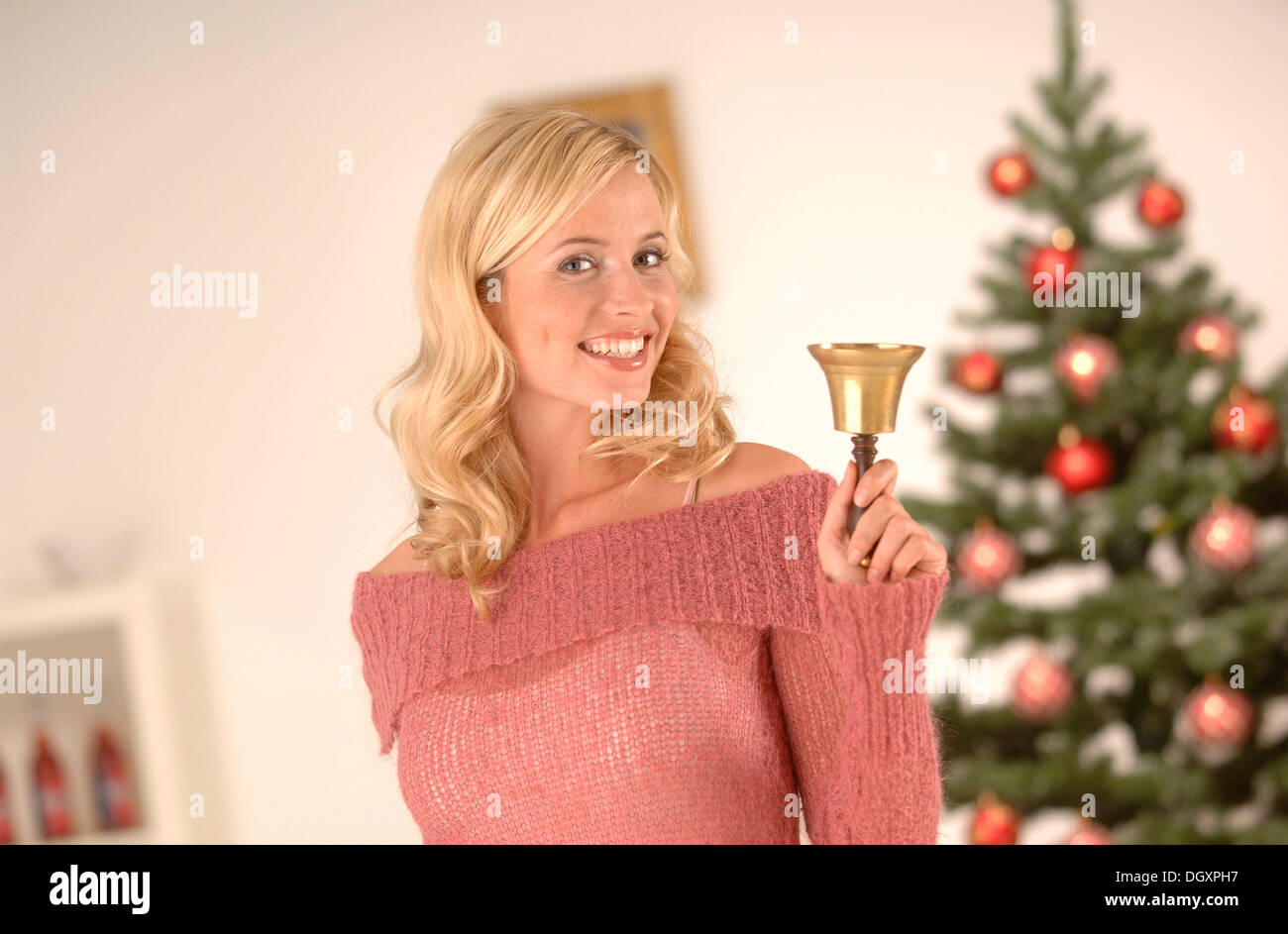 Blonde woman, 20-30, ringing a golden bell, Christmas ambience - Stock Image