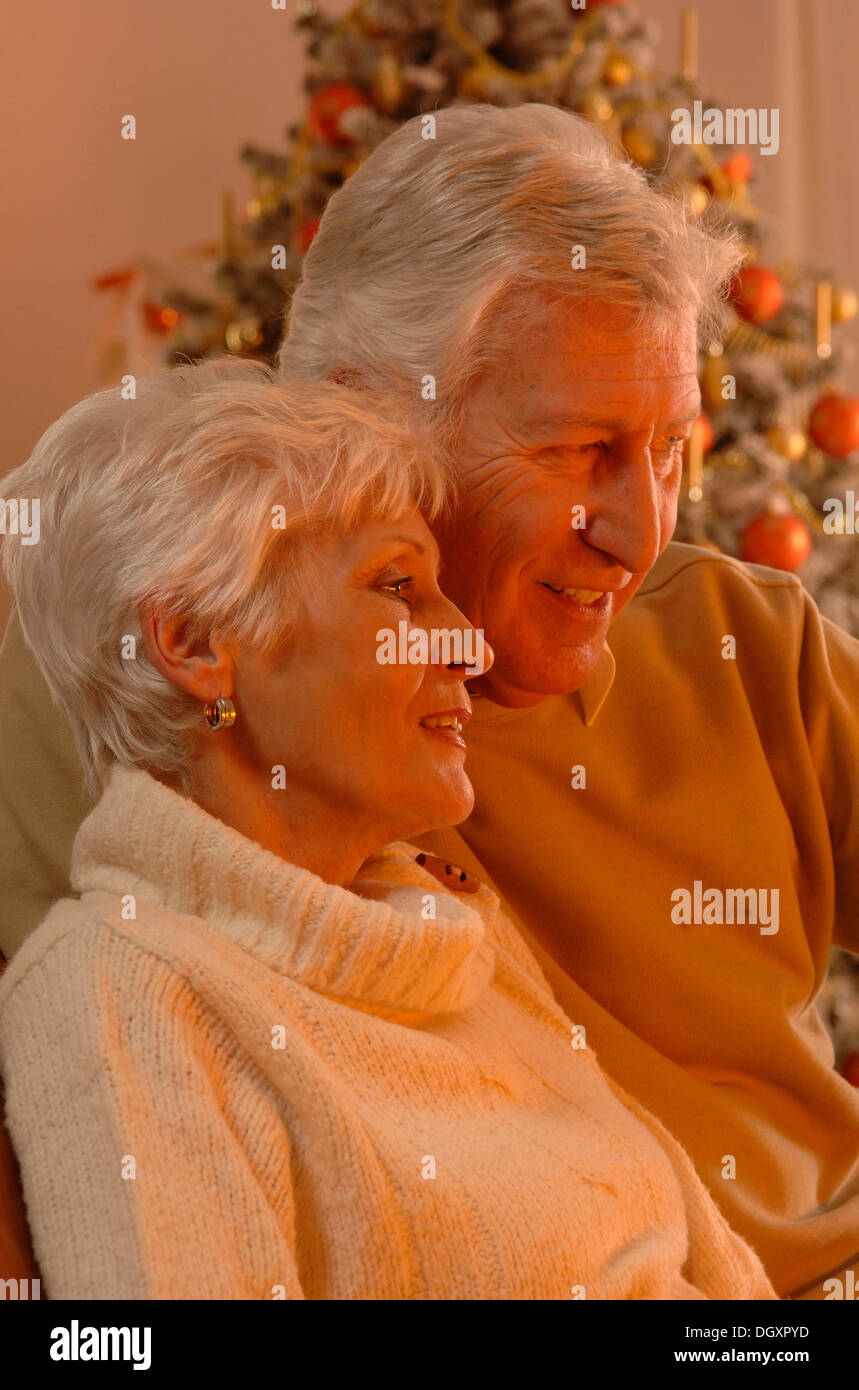 Mature couple in love sitting in front of a Christmas tree - Stock Image
