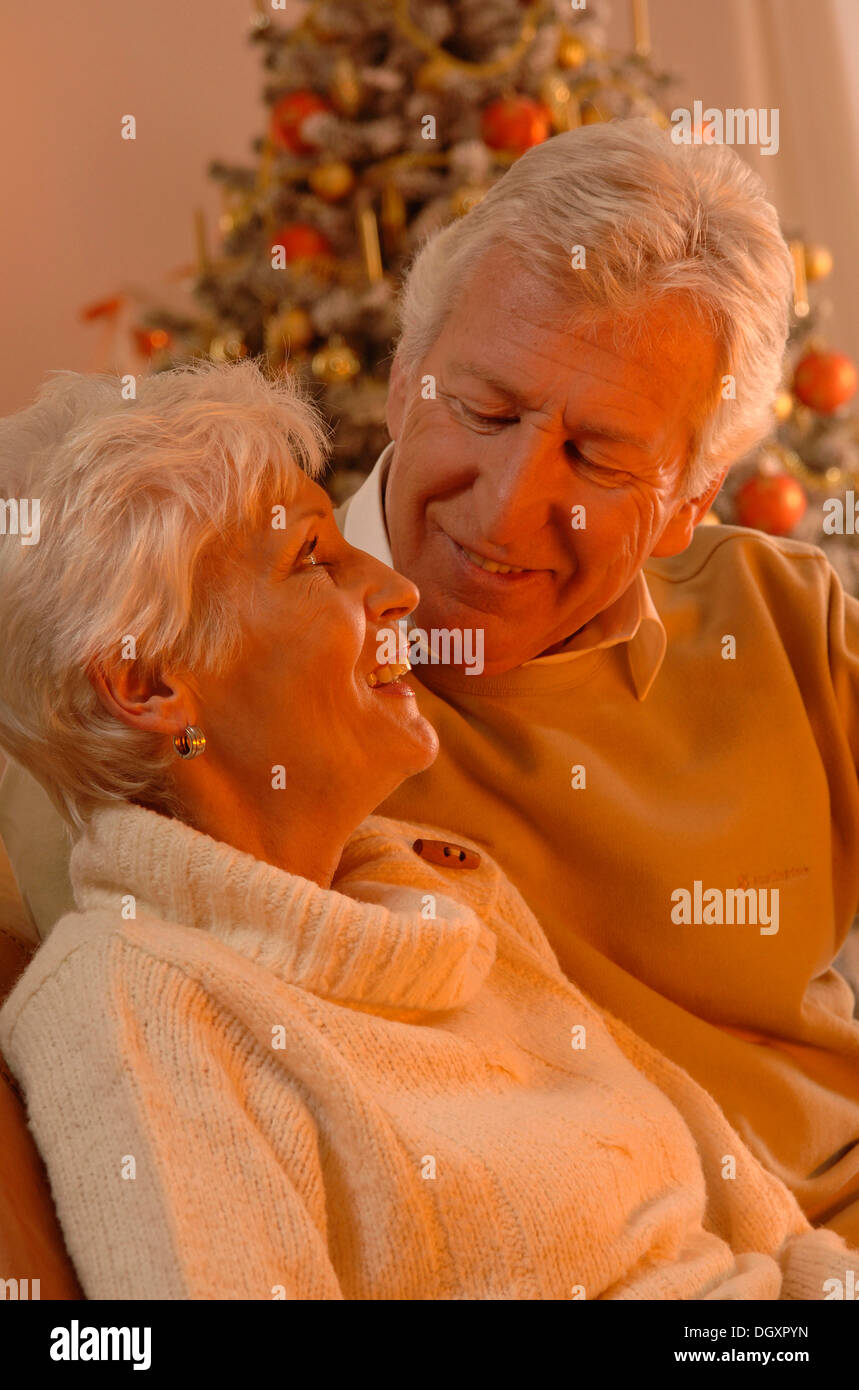 Mature couple in love sitting in front of a Christmas tree Stock Photo