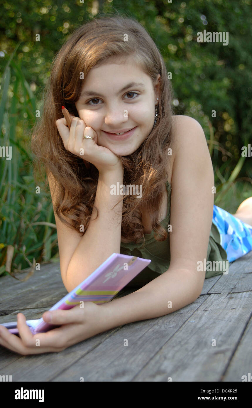 Teenage girl lying on a boardwalk with a book and a pen in her hand - Stock Image