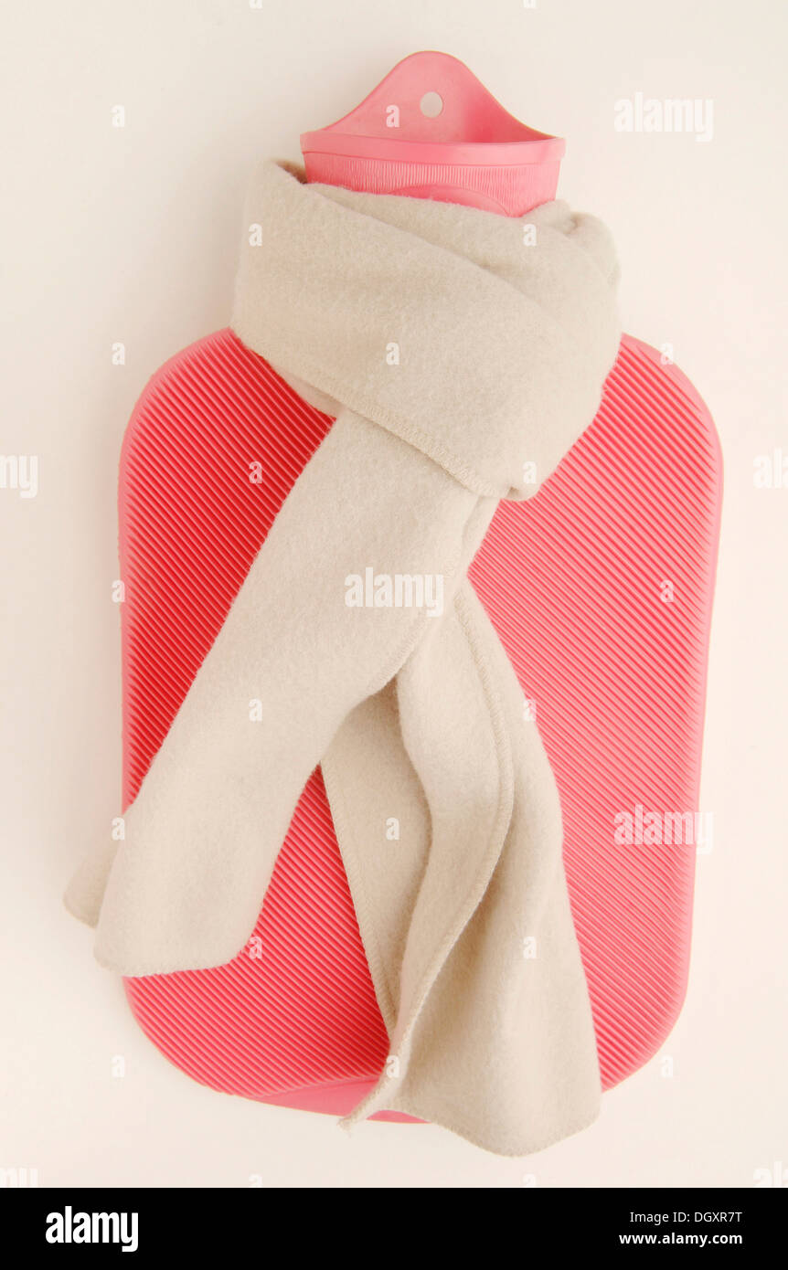 Pink hot water bottle with a winter scarf - Stock Image